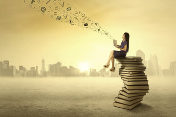 Woman sitting on books and send message