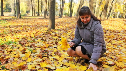 nice woman sits squatted and collects yellow leaves in city park