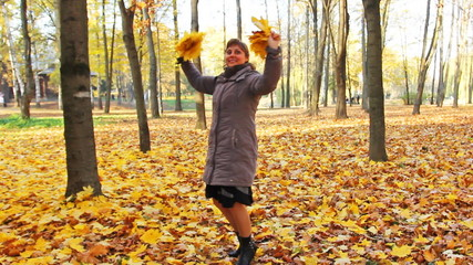 nice woman rotates and scatters yellow leaves in beautiful park