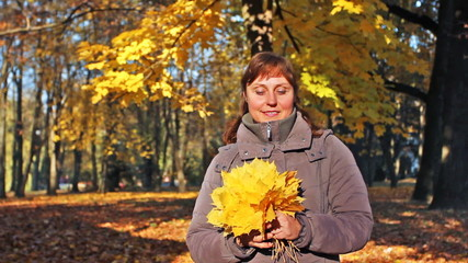 nice woman stands and holds in her hands yellow leaves