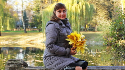 nice woman sits on bench  with yellow leaves near lake