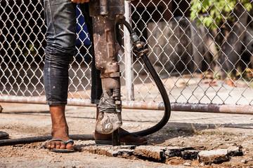 Man drilling cement concrete road.