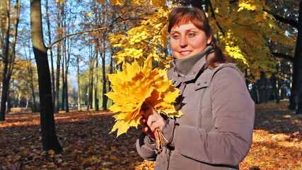 nice woman stands and holds yellow leaves at park