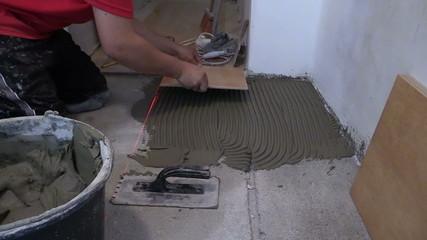 Master man lay ceramic floor tiles in kitchen