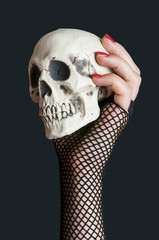 Scull in the hand with red nails on black background