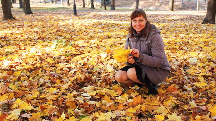 nice woman collects yellow leaves and smiles in autumn park
