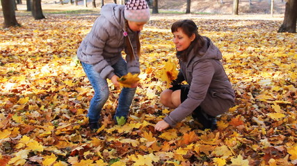 woman with teen daughter collect yellow leaves in autumn park