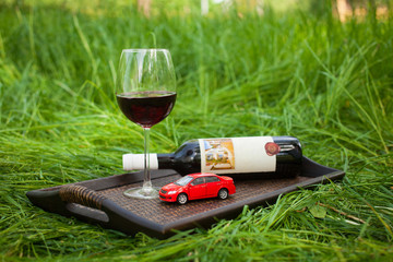 still life with tray, little red car, bottle, glass of wine outd