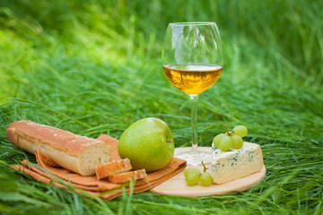 still life with white wine, baguette, cheese, grape and apple