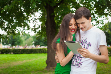 boy and girl in green dress holding ipad together