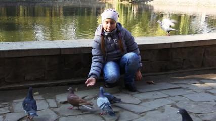 cute teen girl siting feeds pop-corn pigeons in autumn near lake