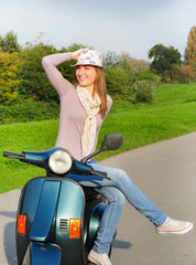 Happy female sitting on vespa scooter holding hat