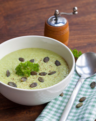 Homemade green broccoli cream soup served in white bowl