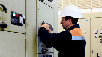 engineer unlocks and activates electrical equipment, closeup