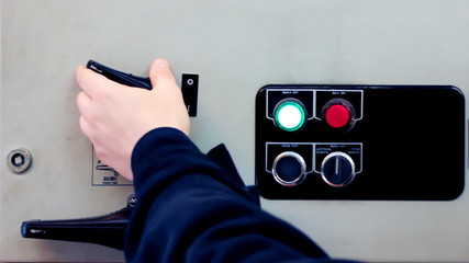 hand of man turns on electrical equipment from control panel