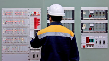 engineer checks indication on two control panels and leaves