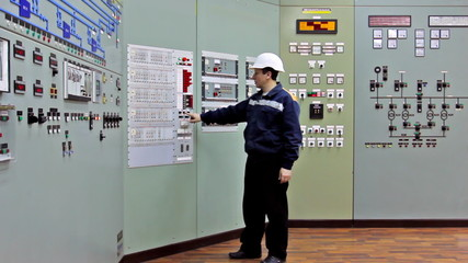 engineer checks indication on two control panels, wide viewing