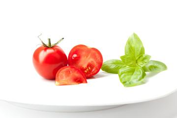 Tomaten und frischer Basilikum auf Teller