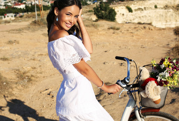 pretty smiling brunette in elegant dress sitting on bicycle