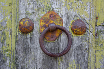 Front view of old doorknocker and painted wooden door