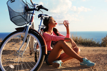 sexy girl drinking water sitting beside a bicycle on beach