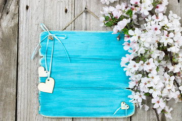Blank antique teal blue sign with hearts and spring flowers