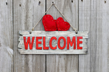 Rustic welcome sign with two red hearts on weathered wooden door