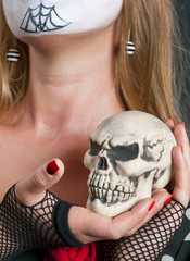 Skull in the hand with red nails of blonde girl in mask