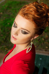 beautiful elegant girl with makeup in a red evening dress