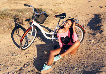 beautiful girl with dark hair sitting beside a bicycle on beach