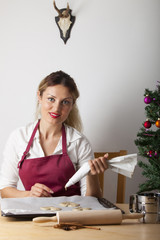 Frau beim Backen mit einem Weihnachtsbaum