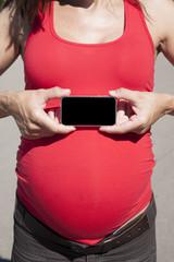 smartphone screen on tummy pregnant woman