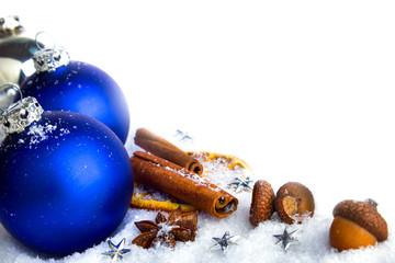 Blaue Wihnachtskugeln auf Schnee mit Eicheln