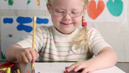 little girl in glasses with a pencil draws - dolly shot