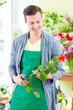 Obrazy na płótnie, fototapety, zdjęcia, fotoobrazy drukowane : Florist arbeitet in Blumenladen mit Blume