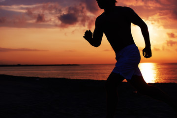Fit man running into colorful sunset along the beach
