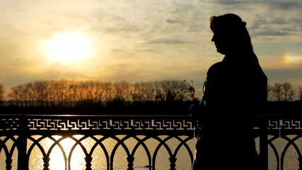 silhouette of lady with flower near clear lake, sunset, close-up