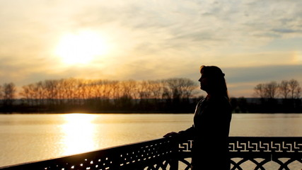 silhouette of pretty lady with flower near clear lake, sunset