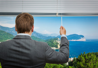 Businessman is looking through the window with sea