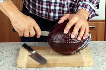 Mann schneidet in Küche Rotkohl auf