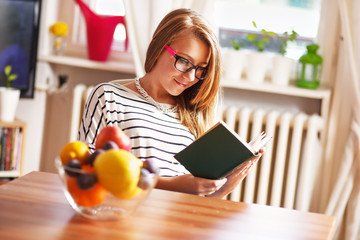 Teenage girl reading book, at home