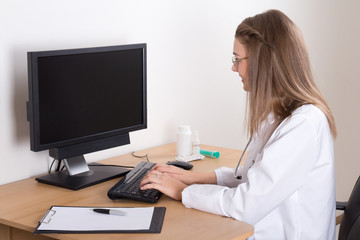 young woman doctor using computer in office