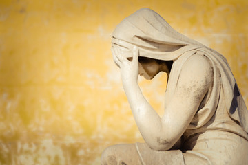 Vintage statue of a crying woman with a grunge wall background