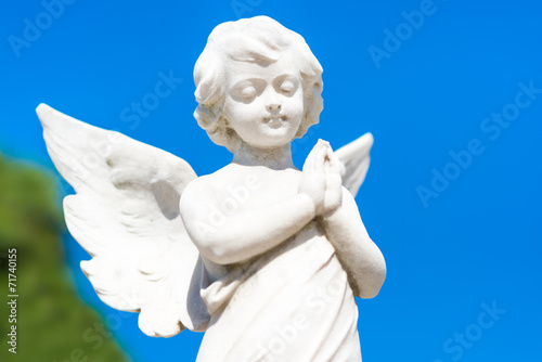 Beautiful infant angel on a blue sky background