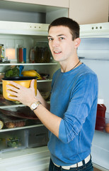 Handsome man with saucepan  near refrigerator