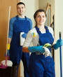 Smiling cleaners team at door