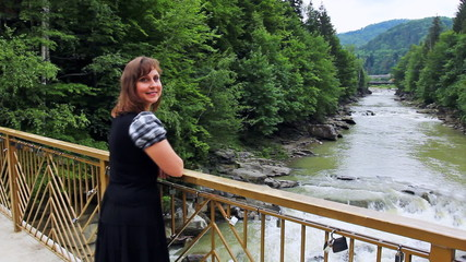 pretty woman stands on bridge and looks on waterfall