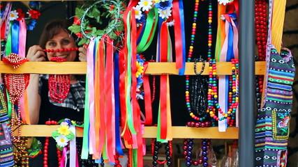 pretty woman tries Ukrainian folk ornaments on market
