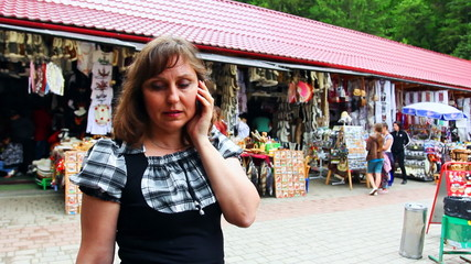 nice woman speaks by phone on Souvenir Market Yaremche, Ukraine