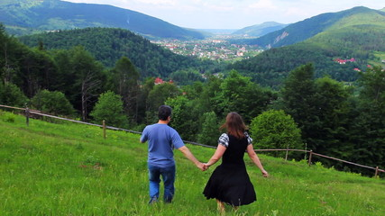 loving couple holding hands going down to beautiful mountains